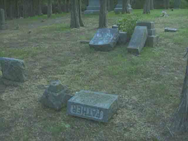Grave markers knocked over due to vandalism