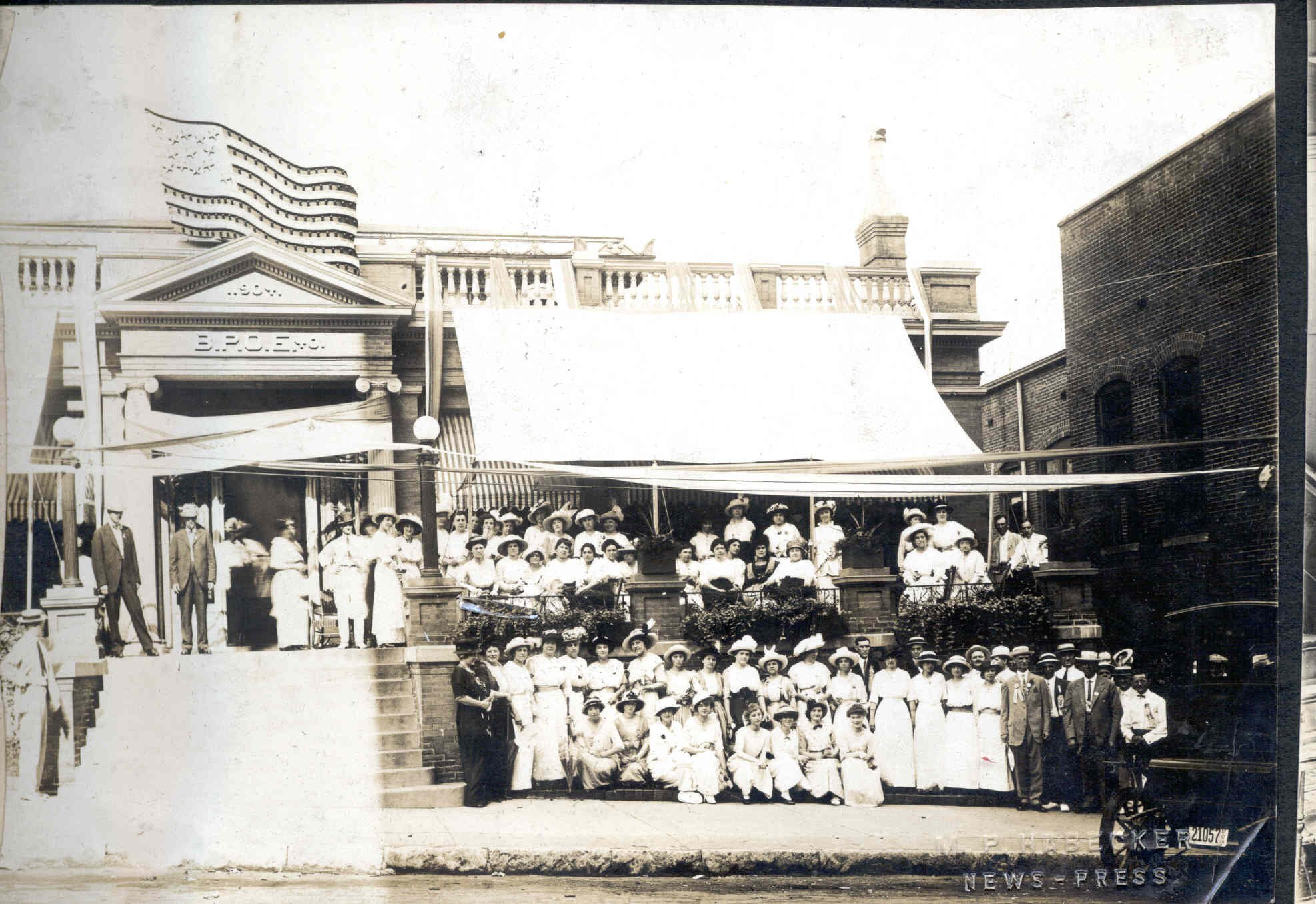 Elks Lodge Women's Group Photo, c. 1920s.  b/w.  A large group of women in white long dresses/hats posed on the sidewalk and porch of Elks Club Building, a few men in the photo.  Image provided by the St. Joseph Museums, Inc.