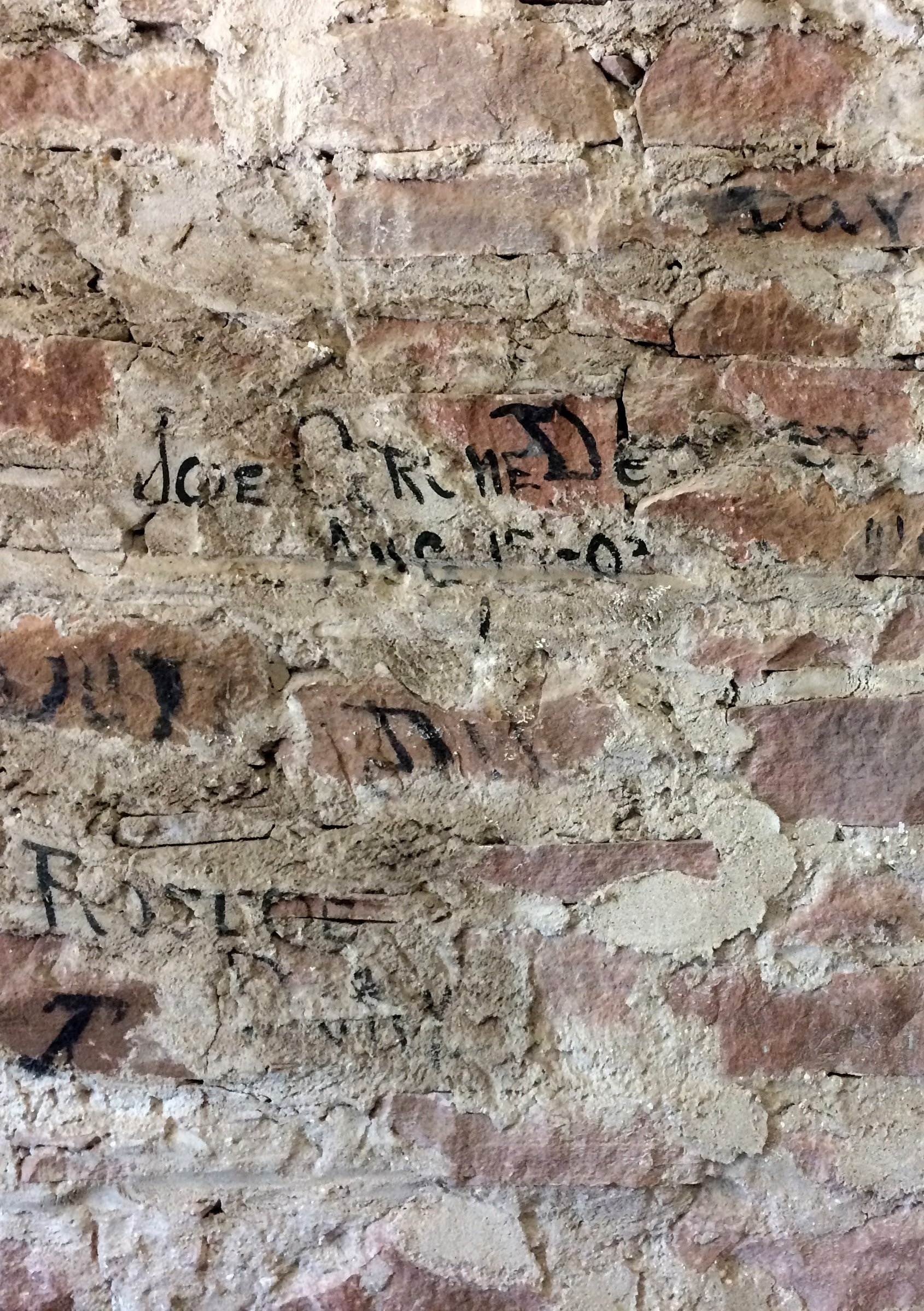 This photo is of an interior wall in the baggage room. During one of the renovations, crewmen's painted initials were discovered. 