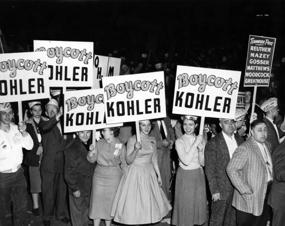 Women hold signs in support of the 1954 Kohler strike