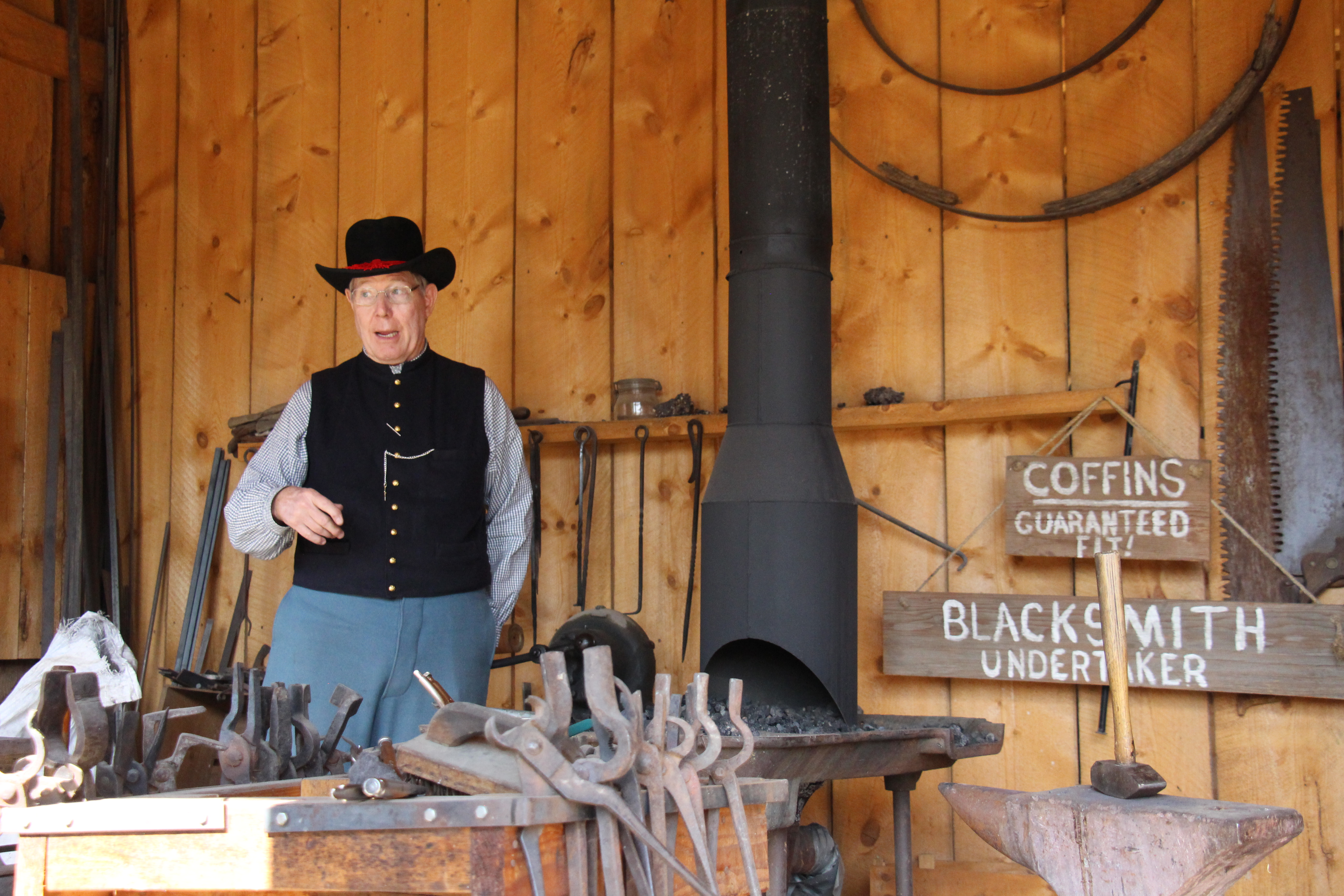 One of Four Mile's docents and blacksmiths explains the process to visitors
