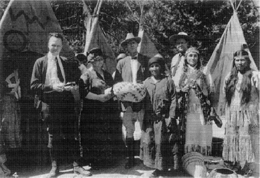 The winner of a basket weaving competition poses with visitors and park officials.