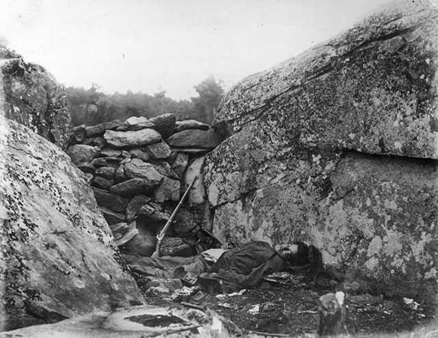 This photo was taken of a soldier who had died during the fighting at Devils Den: http://abcnews.go.com/blogs/headlines/2013/07/the-legacy-of-gettysburg/