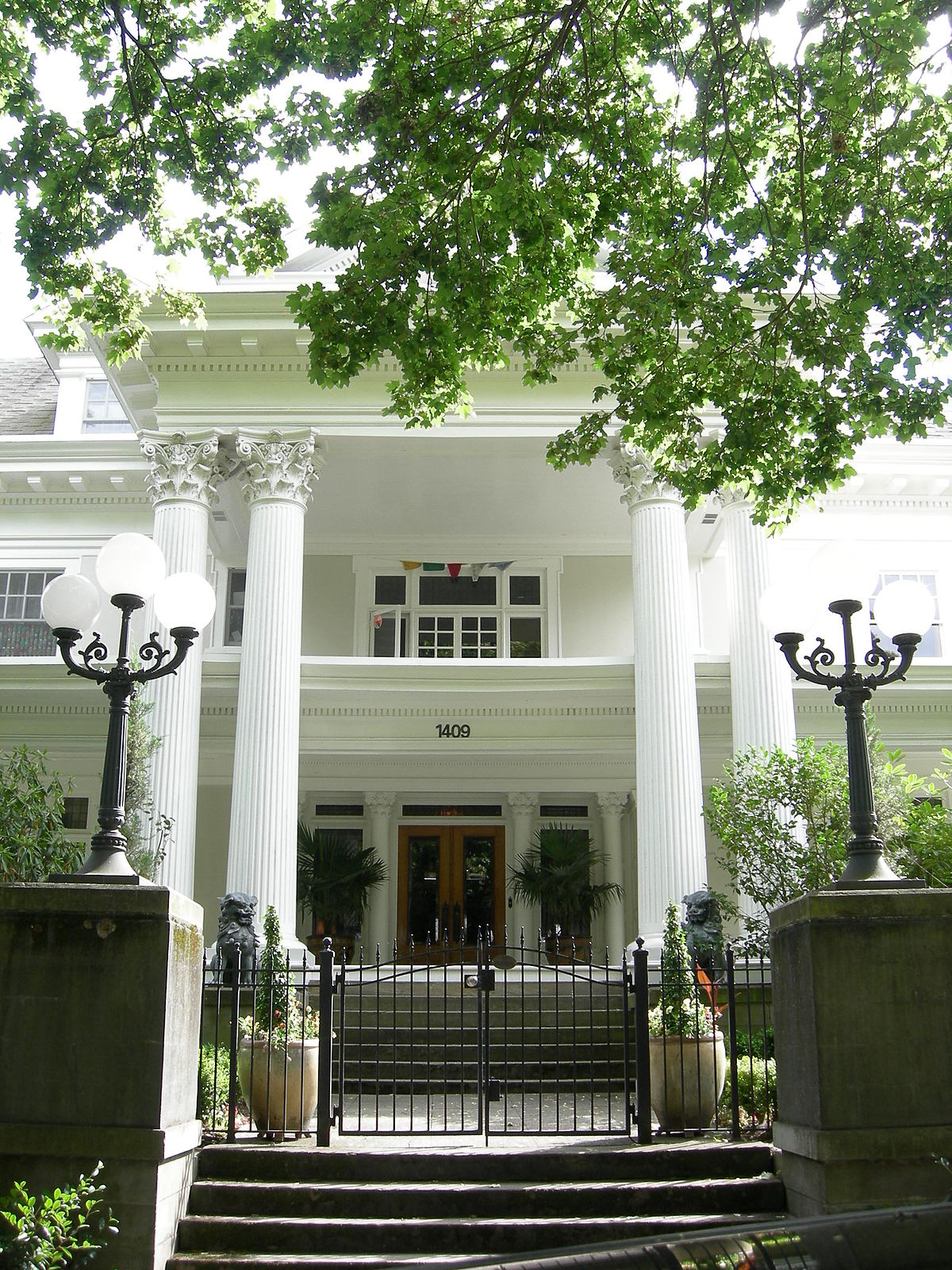 A frontal view of the estate highlighting its grand white columns and entryway. The original architect, Frederick Sexton, was known for creating lavish residences: much of what attracted George Parker to buy the home.