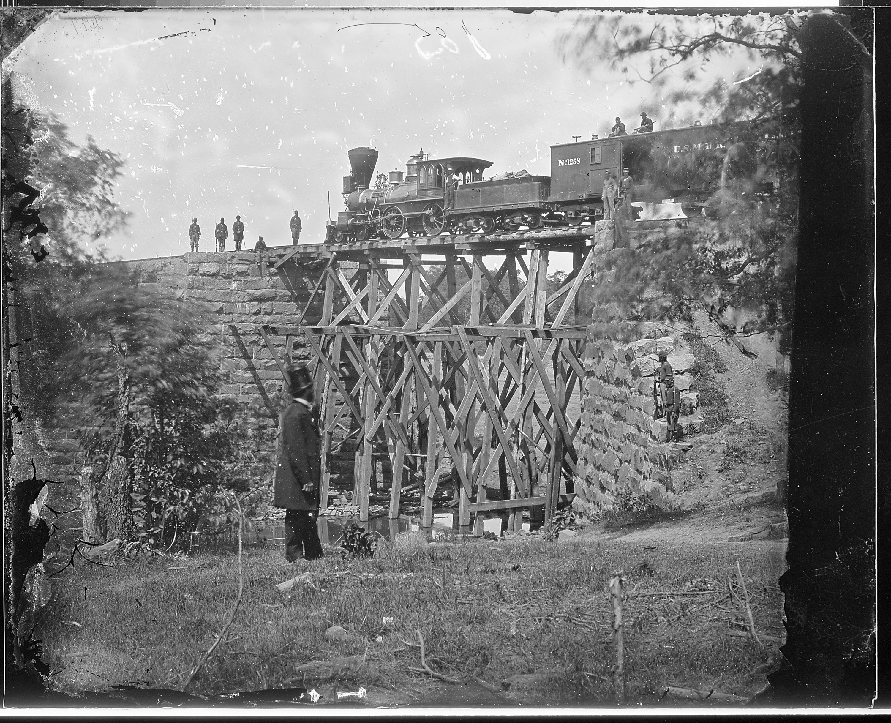"This picture is widely reported as being of the original Accotink Bridge, and it is included on several markers. However, other sources dispute the claim. The picture, taken by Matthew Brady or one of his associates, is simply labeled ""Cars of U.S. Military R. R., and bridge built by Soldiers. Orange and Alexandria R. R."" by the National Archives."