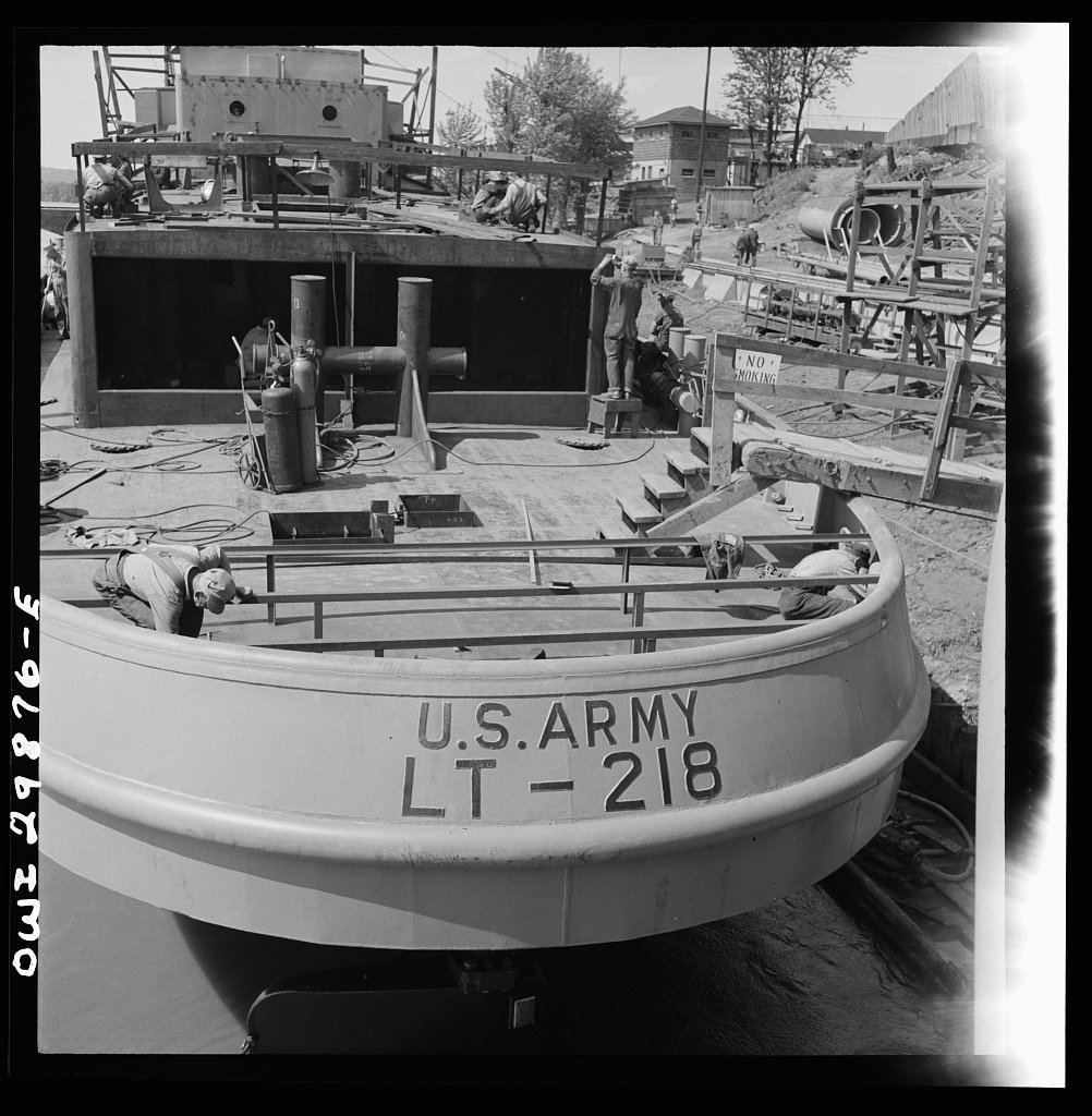 "Workmen clamber over a U.S. Army boat (LT stands for ""large tug"") under construction at Marietta in 1943. Launched in August of that year, LT-218 was later sold to China in 1947."