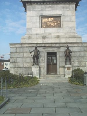The Eakins bronze relief plaque in this front view depicts the opening of the Battle of Trenton. The central entrance door is flanked by a pair of bronze, full-length figures of Continental soldiers.