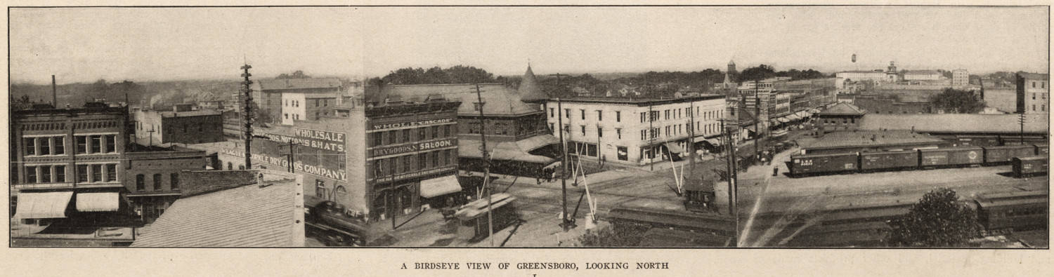 A panoramic view looking north from the railroad tracks into downtown Greensboro, showing in foreground the Cascade Saloon and Southern Railway station, among other buildings