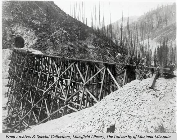 An image of a treeless and barren valley and tunnel and train tracks impacted by the 1910 fires.