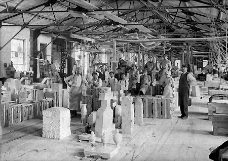 Proud craftsmen from many lands stand behind their handiwork in the marble finishing shed at Middlebury's Marble Works, circa 1900