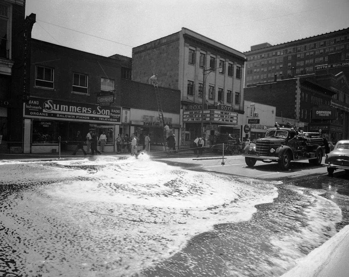 Water from a fire hydrant floods the street during the August 1952 fire