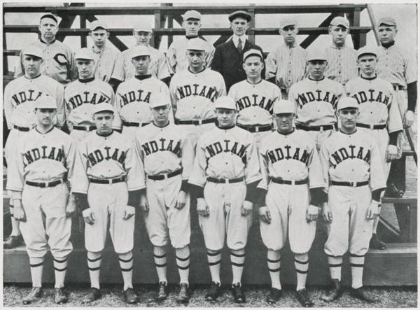 The 1920 Indiana Baseball Team standing on bleachers which were nonexistent in Indiana Baseball's early days. The uniforms have a much more modern look than past designs.