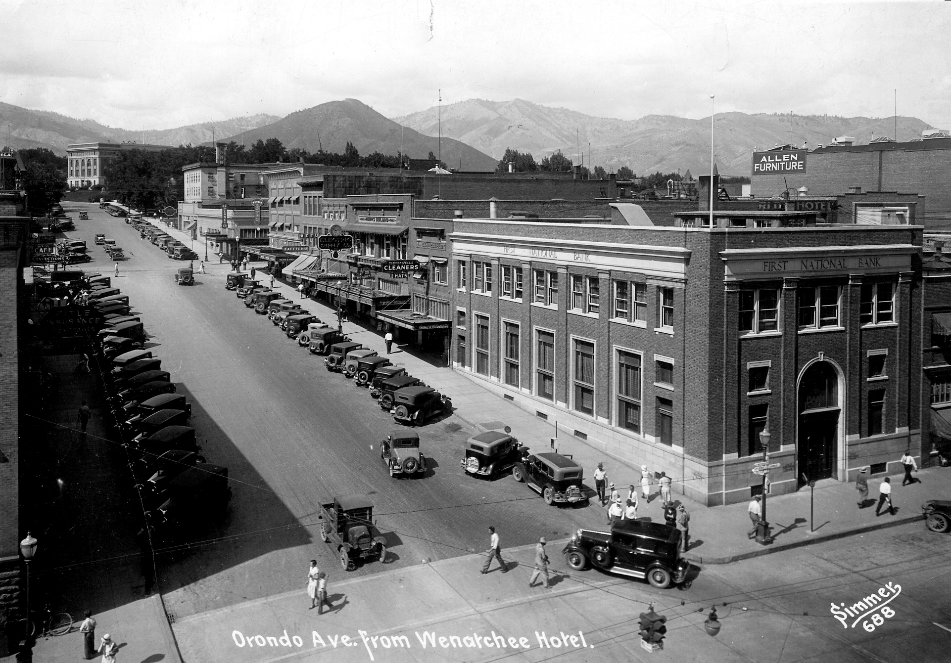 Looking up Orondo Avenue from intersection with Wenatchee Avenue: First National Bank; Nancekivell Building; Nancekivell's Cleaners; Phipps Building; Electric Supply Company; W.C.T.U. Building; Women's Christian Temperance Union (W.C.T.U); Morton Building; Harlin Hotel and Building.  Across South Mission Street is J. C. Penney; Elks Building.  Across South Chelan Avenue is Memorial Park and the Chelan County Courthouse.  To the right is Allen Furniture sign on building; large number of automobiles visible and pedestrians.   This version of the building stood at this location until 1974.