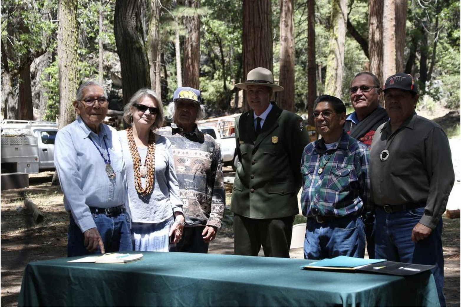 Superintendent Michael Douglas poses with members of the Mariposa Indian Council after returning possession of the Indian Village back to the council.