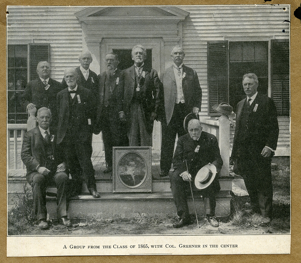 A group from the class of 1865 with a framed photograph of Richard Greener in the center, 1915