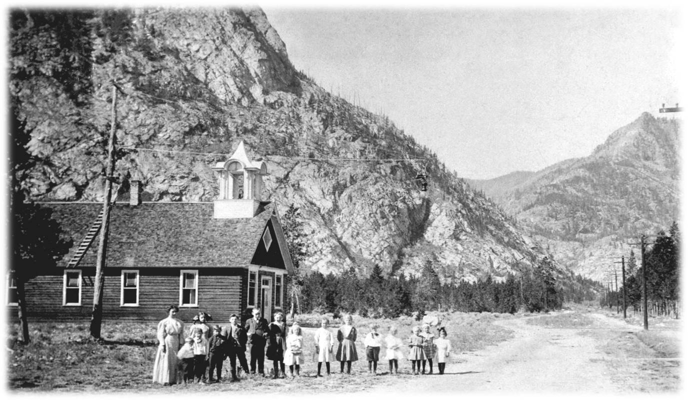 The Frisco Schoolhouse with Miss Lynch, teacher, and a group of 15 children. Note the telephone poles and the Victorian era cupola. Circa 1910