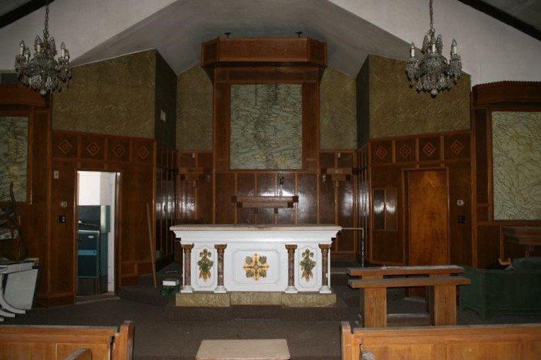 Interior features: the altar, inlaid wood paneling along the back wall, and chandeliers