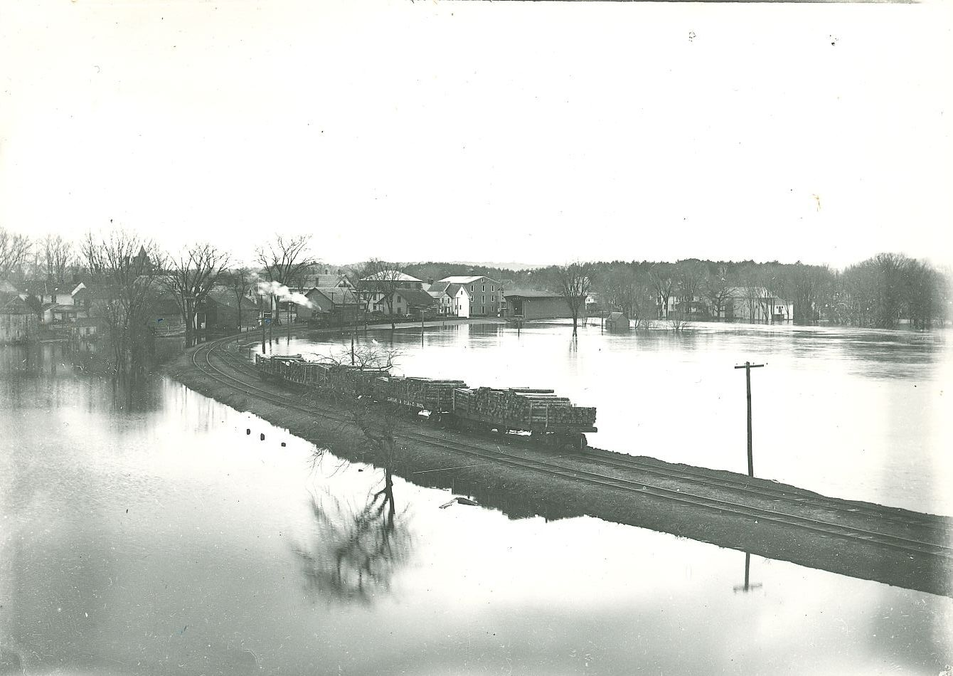 Undated image of a train full of lumber heading into the Contoocook Depot with high waters on both sides of the track.