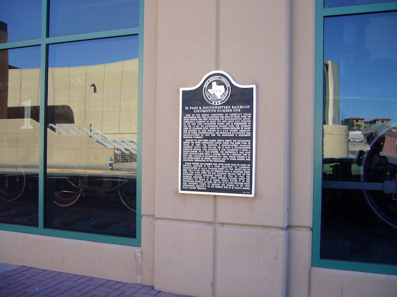 The historical marker is located outside on a column between two windows.