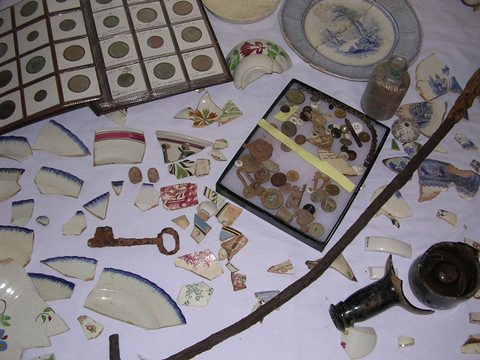 Some of the artifacts found during demolition/rebuild of McAtee's Tavern. Note the book of coins in the upper left corner of the photo. Most of these dated from the operation of the tavern, a finding consistent with having paying customers frequent the building.