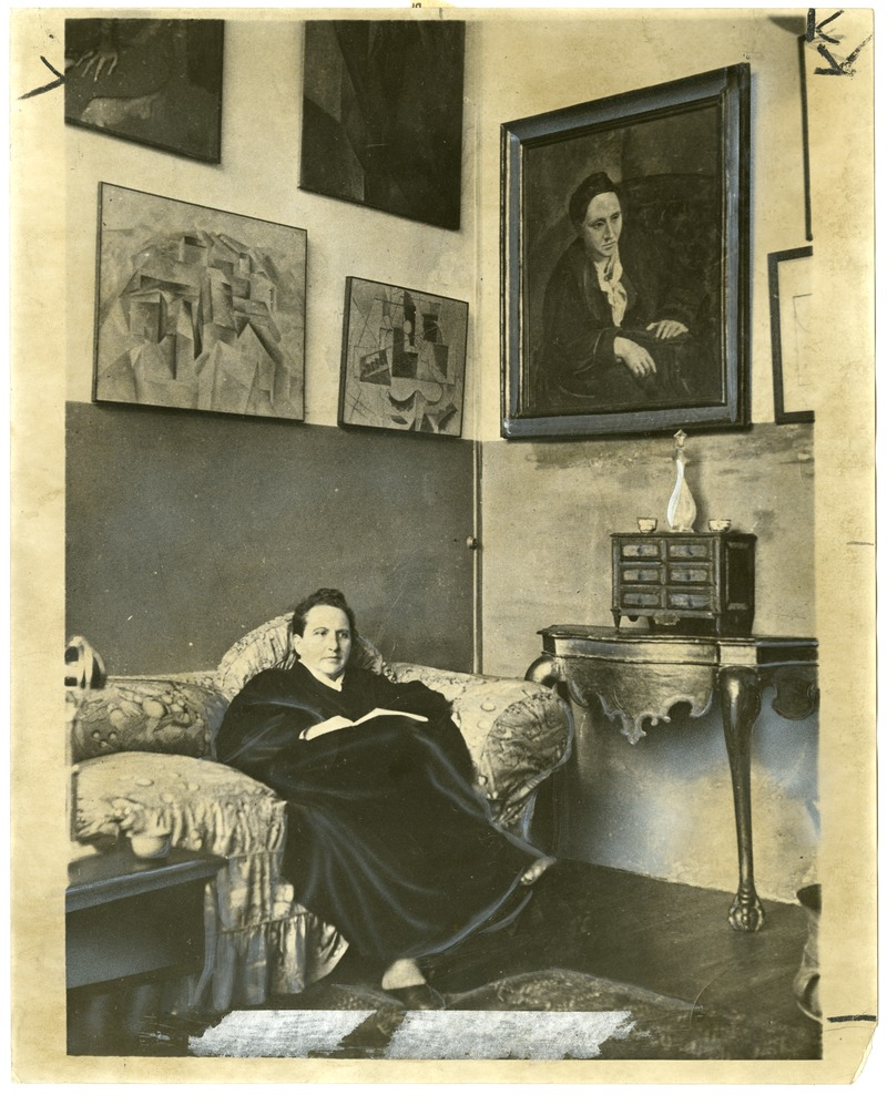 """Gertrude Stein sitting on a sofa in her Paris studio..."""