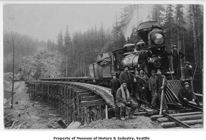 Group of construction workers posing in front of a Northern Pacific engine, #457, and caboose, at the Green River Crossing, 1885