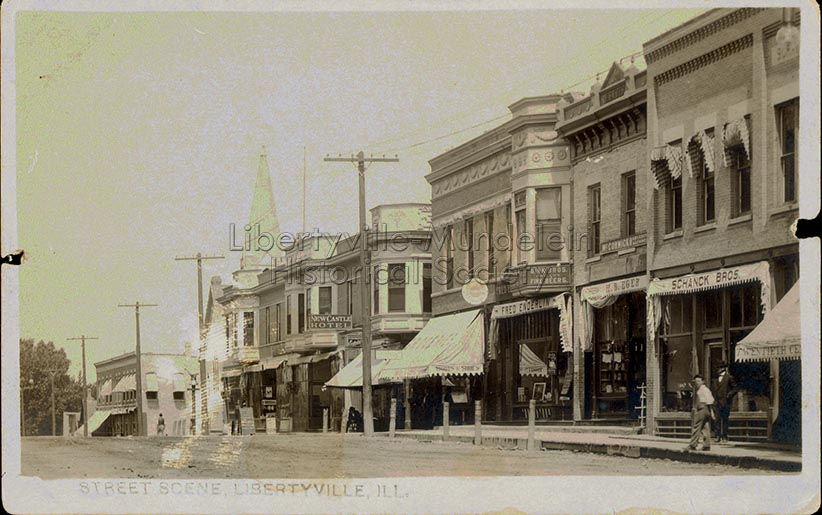 Looking north on Milwaukee Avenue, before 1913. Storefront canopies for E.B. Eger and Schanck Bros. visible