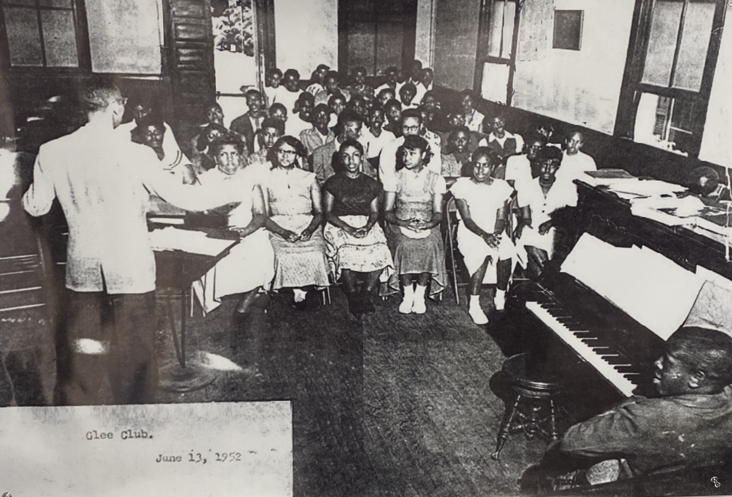 Pictured is a Glee club practice in the nearby church. The church provided extra space for activities when the school began to experience over crowding.