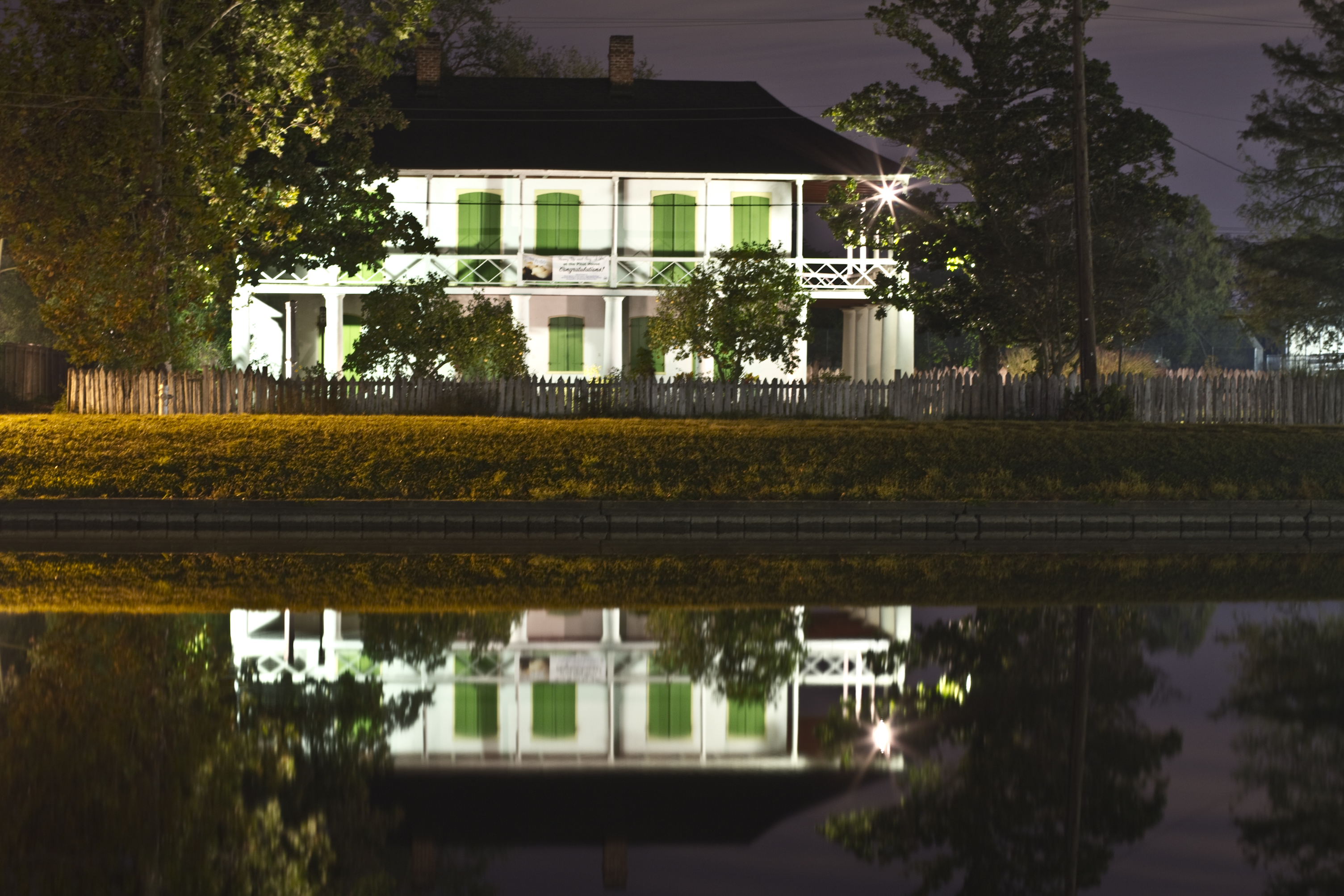 Pitot House is reflected in the waters of Bayou St. John.  It is easy to see why it is often used as a special events venue.