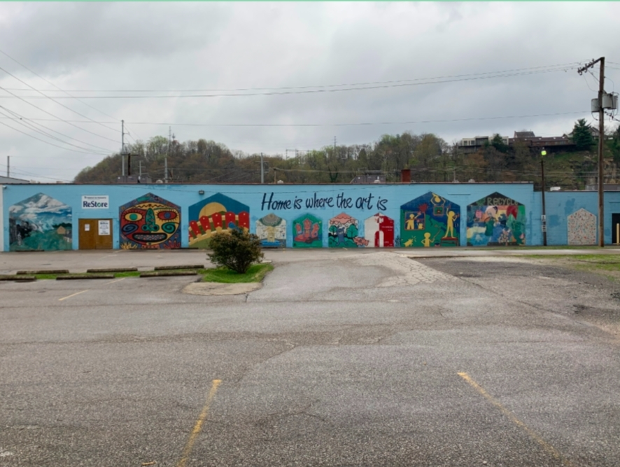 A mural faces a small empty parking lot on the back of a one-story building.