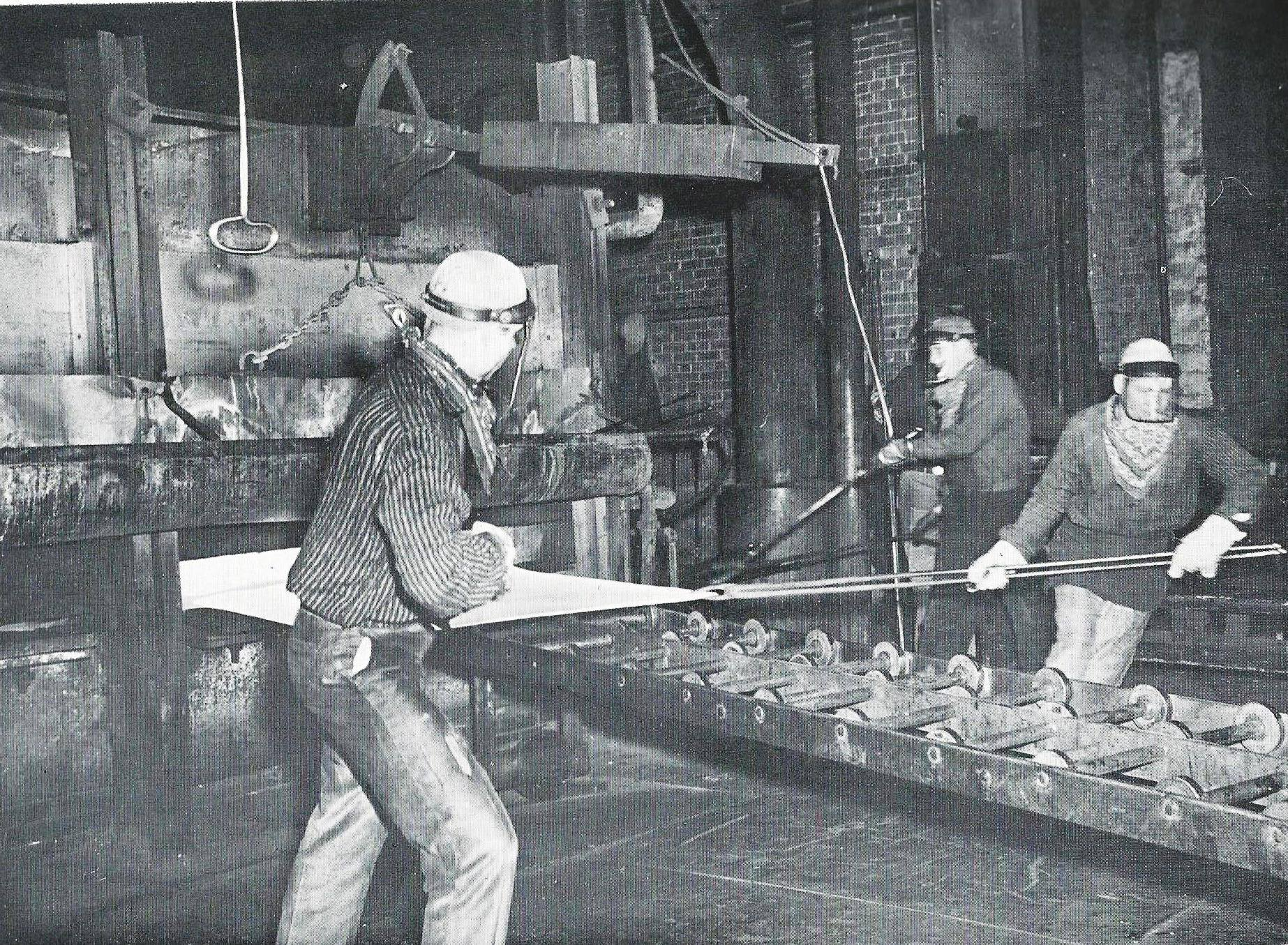 Workers pull a sheet of metal out of an annealing furnace, 1966