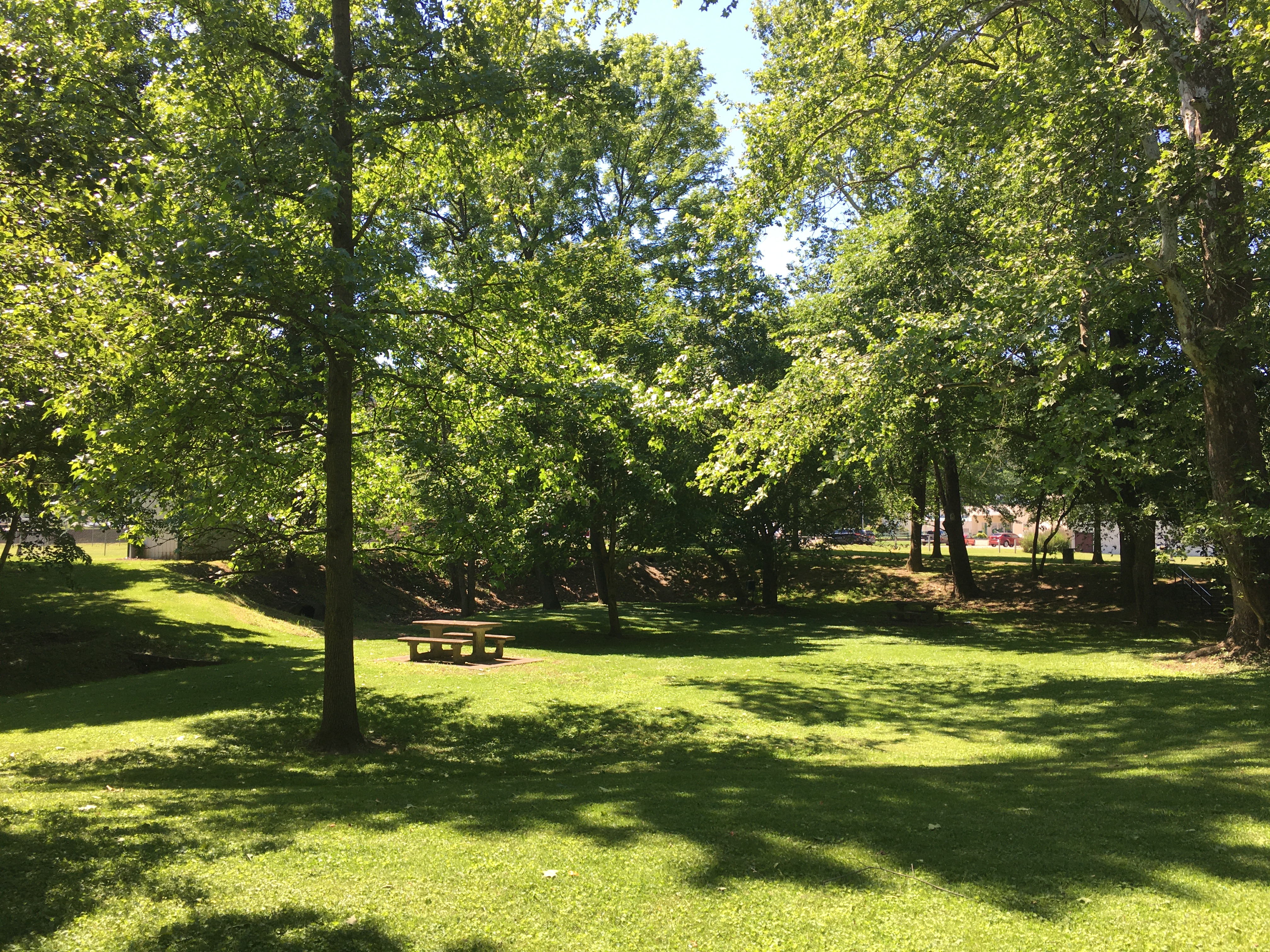 The park includes a walking trail, picnic tables, and green space for recreational activities.