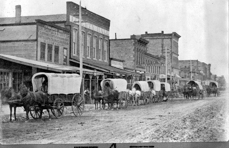 1870s-early 1880s photo of wagon train along Massachusetts St. - Old Liberty Hall behind pole (KSHS)