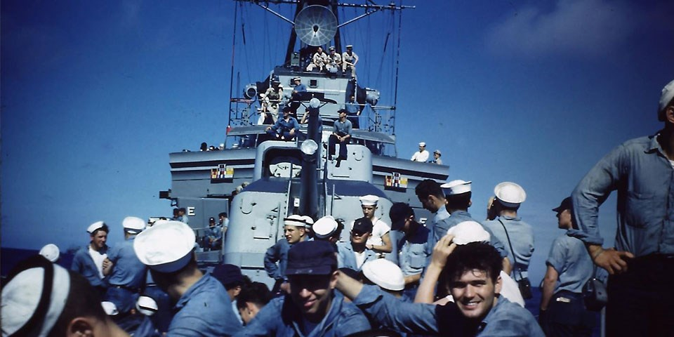 """Photograph from the bow of Cassin Young looking aft with crewmembers on the deck, guns, and bridge. Crew are wearing dungarees and a few officers are wearing khaki uniforms. Crew members on the bow of USS Cassin Young during a cruise in the late 1950s."""