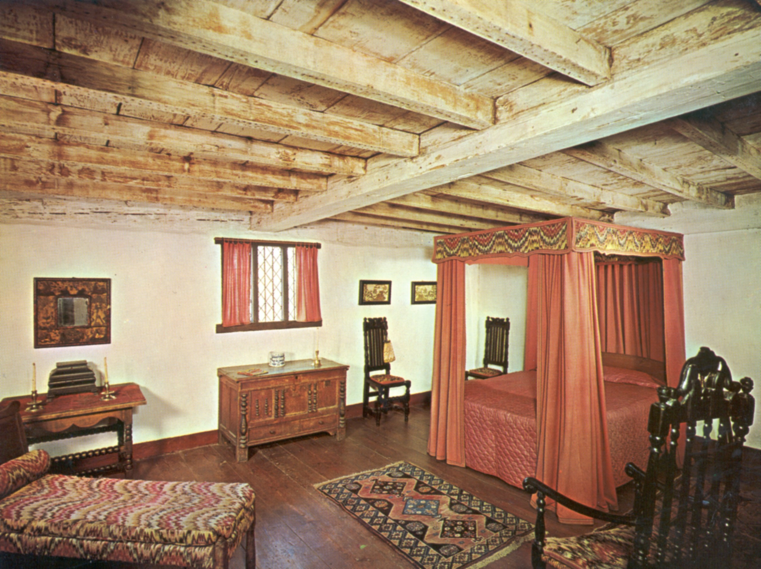 The second floor best bed chamber features 18th century furnishings and hewed, exposed beams.