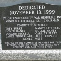 A stone carved with details about the memorial's dedication.