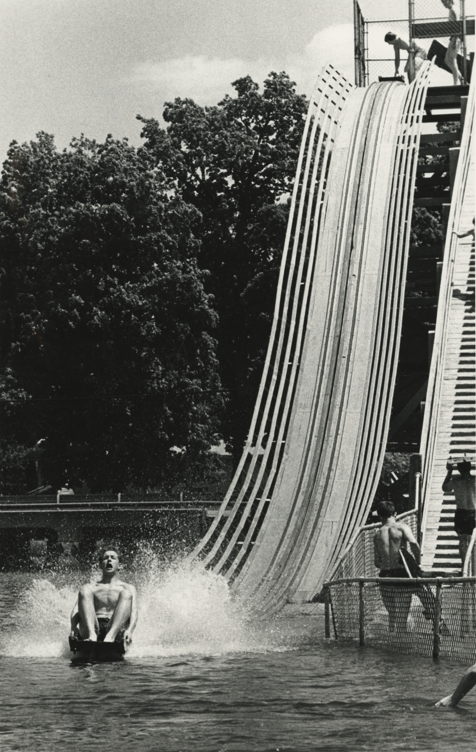 """""""Many area residents took advantage of Saturday's summer weather for a day in the park. The giant slide at Lake of the Woods Park in Mahomet was one well-used attraction during the hot afternoon."""" Urbana Courier, June 4, 1978 (Photo courtesy of the Champaign County Historical Archives, Urbana Free Library)"""