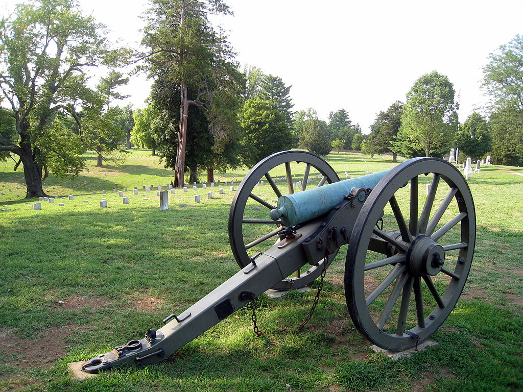 """A cannon representing where Confederate General James Longstreet's cannon were located with his men in front along the stone wall. Headstones of the cemetery can be seen in the background. This section is called """"Longstreet's Line."""""""