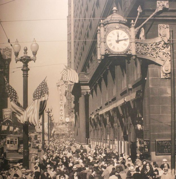 Pedestrians walk past and gather under one of the store's iconic clocks