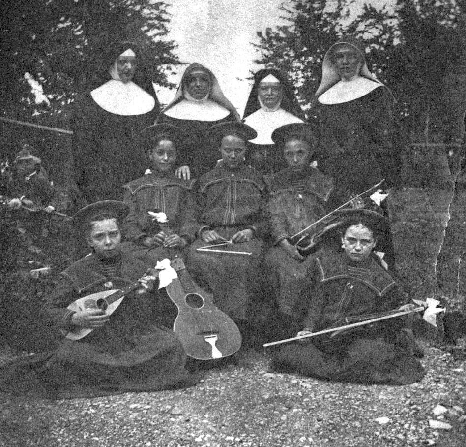 Mother Agnes Hazotte, Sister Ambrose Gross (center), and two visiting sisters with some music students, 1890s.