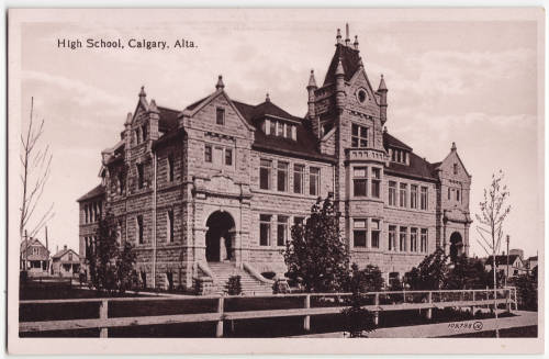 """""""Postcard. Black and white photograph of Central High School in Calgary. A fence can be seen lining the front entrance and two houses are visible on the left hand side. Red text on front (top): 'High School, Calgary, Alta.'"""" pc_164"""