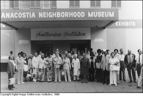 An early photo of the museum, then named the Anacostia Neighborhood museum, with patrons standing outside it.