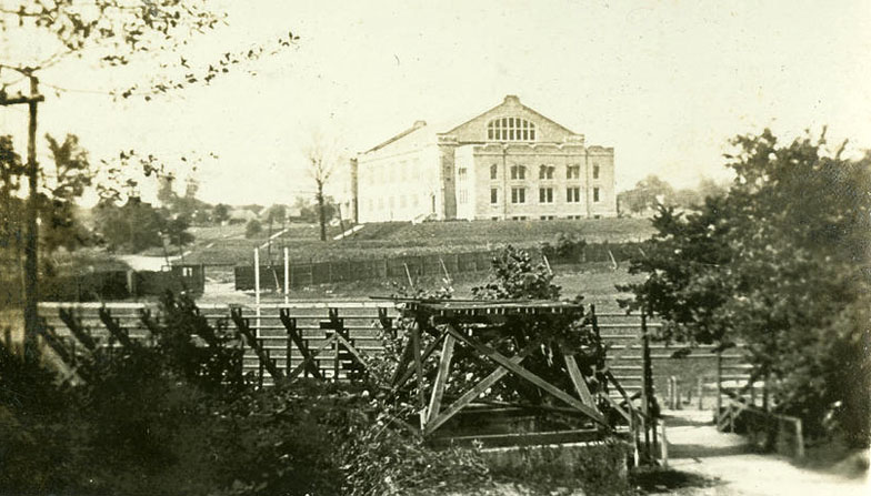 A land view of Jordan Field behind the bleachers. In the background, fencing is seen around the perimeter of the field. The building in the background is what is now known as the Wildermuth Intramural Center.