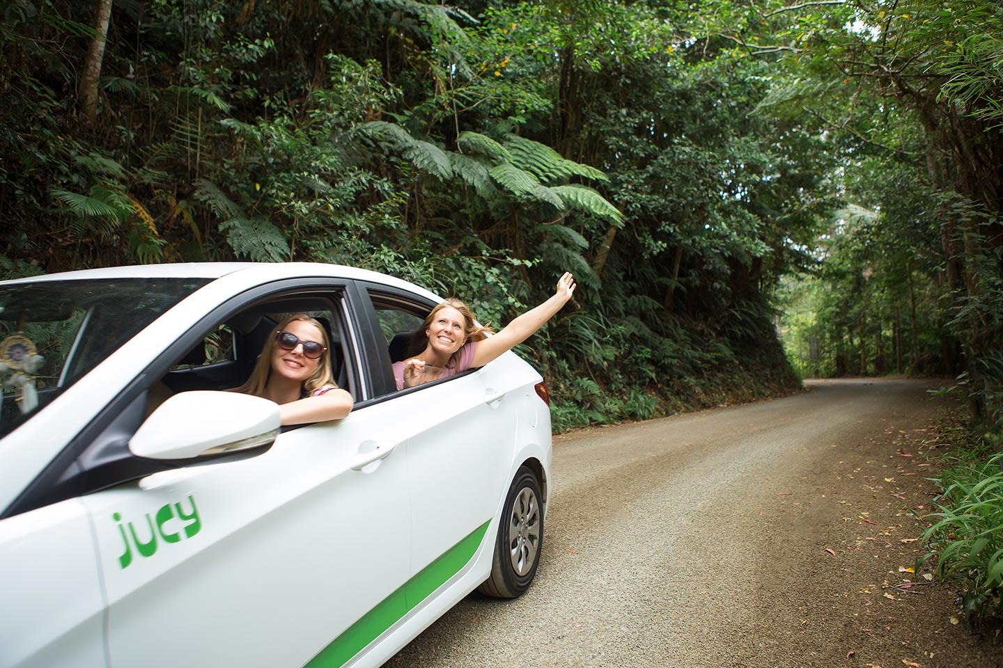 friends driving through forest road having fun
