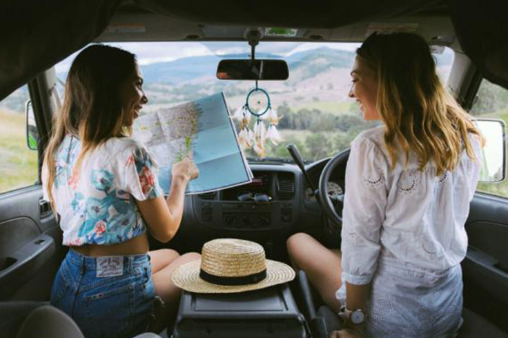 2 girls looking at a map in a campervan