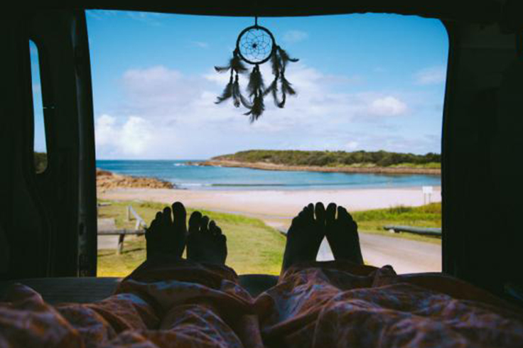 2 people waking up to a beach view in a campervan