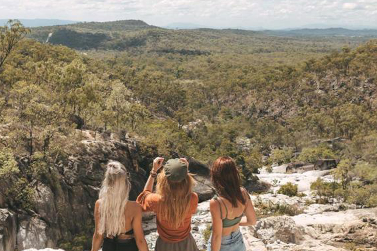 girls taking a photo at emerald creek falls in queensland