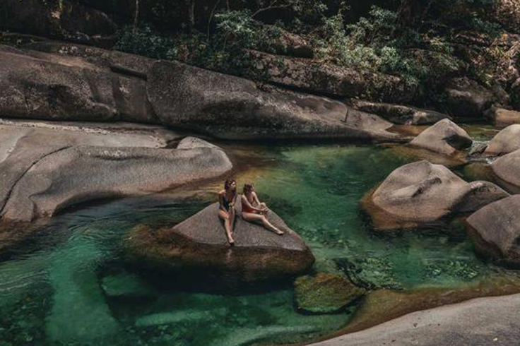 2 girls sitting on a rock in natural pools