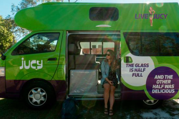 Girl sitting in a JUCY campervan