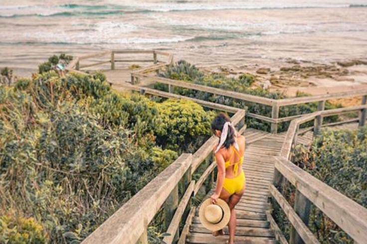 girl in swimsuit walks down steps at beach in australia